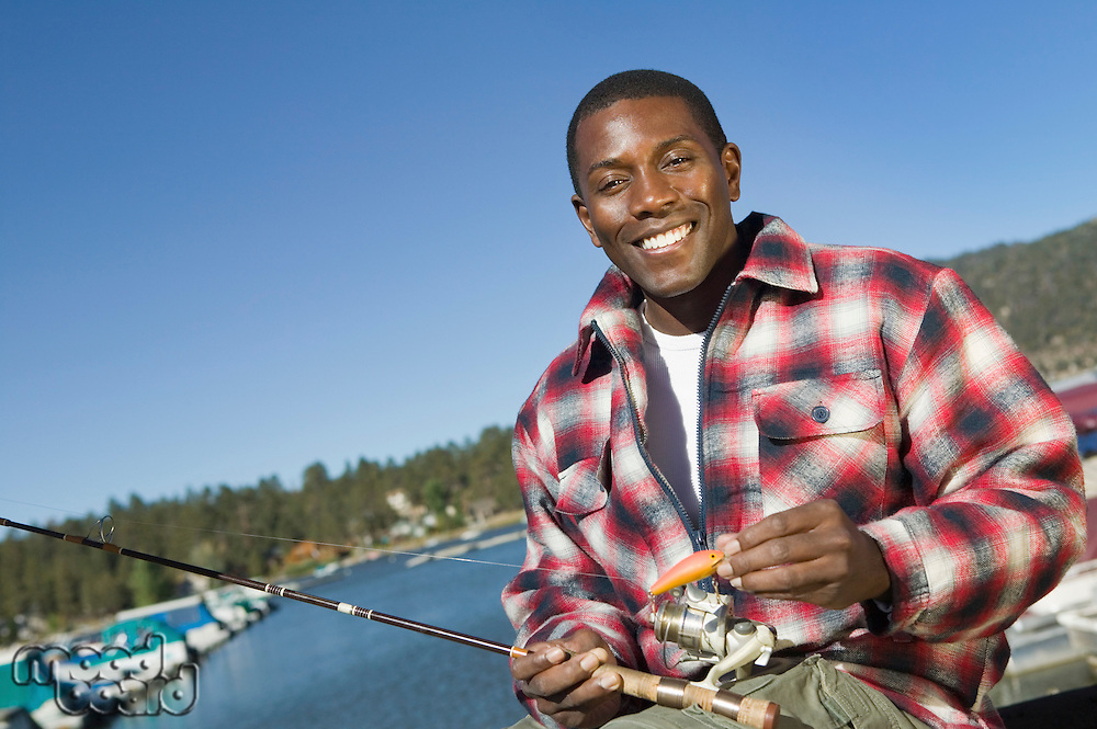 Man with Fishing Pole and Lure at Lake