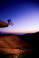 Low angle view of a young man jumping his mountain bike off a water storage tower near Santa Barbara, California. (releasecode: jk_mr1026) (Model Released)
