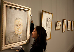 © Licensed to London News Pictures. 01/02/2012. LONDON, UK. A member of Sotherby's staff adjusts Lucian Frued's 'Portrait of a Man' as it hangs with  5 other pieces of his work at an auction of Impressionist and Modern Art held on the 15th of February 2012. The painting, never seen before in public, depicts Bernard Walsh, who's Soho restaurant was frequented by artists, including Freud throughout the 1950's and 60's, and is estimated to raise £1,5000,000-2,000,000. Photo credit: Matt Cetti-Roberts/LNP
