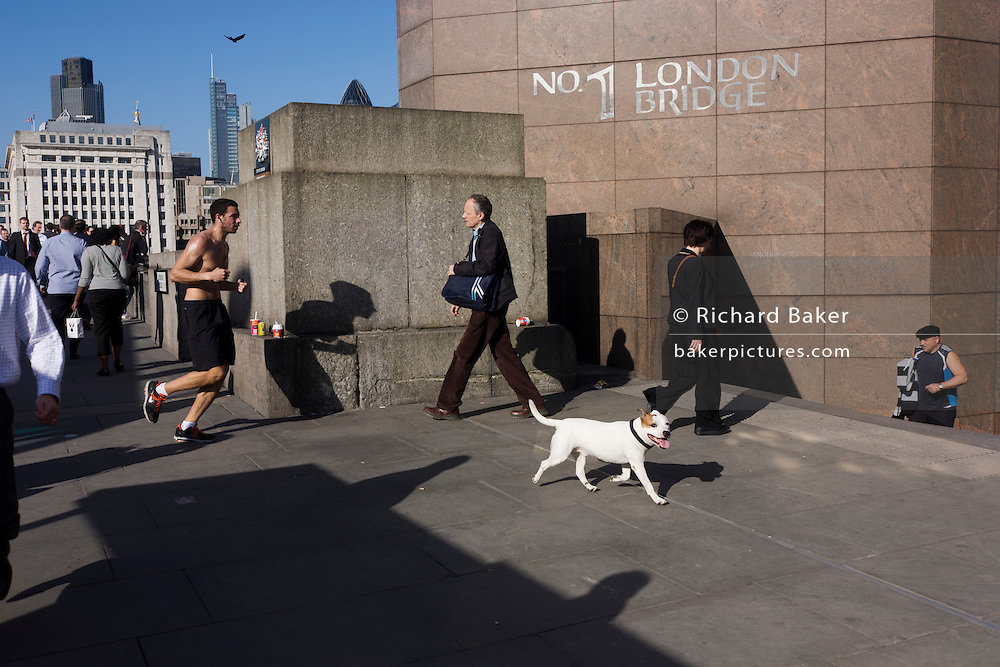 Commuters, jogger and and passers-by at the griffin boundary of the City of London limits on London Bridge.