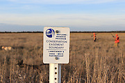 With signage visible in the foreground, hunters work a piece of land enrolled in the Wetland Reserve Program