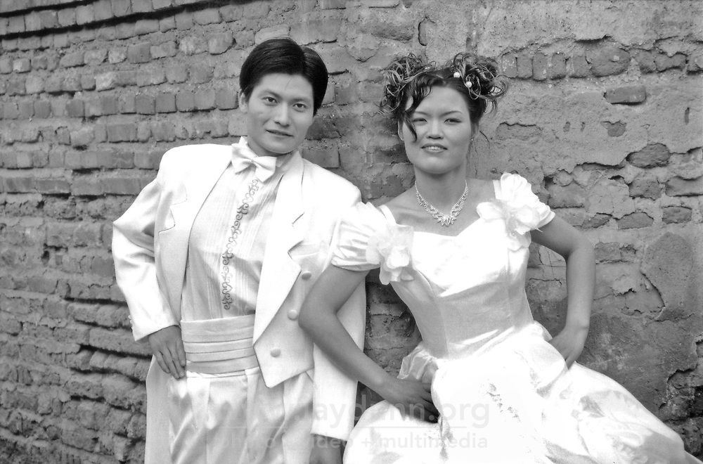 "China, Beijing, 2008. Bride and groom pose for wedding photographs outside their parent's modest home in one of Beijing's ""hutongs,"" or traditional neighborhoods."