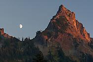 The moon rising over Pinnacle Peak of the Tatoosh Range in Mount Rainier National Park, Washington State, USA.  Photographed near Reflection Lakes.