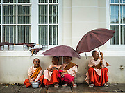 20 OCTOBER 2015 - YANGON, MYANMAR:   Buddhist nuns wait out a rain storm in Yangon, Myanmar. PHOTO BY JACK KURTZ
