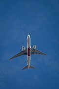 A Boeing 777-F1H jet airliner (A6-EFF) with Emirates flies overhead in blue skies on its flight-path into London Heathrow airport, on 8th August 2018, in London, England.