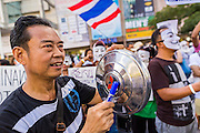 "09 JUNE 2013 - BANGKOK, THAILAND:  A Thai ant-government protester in the White Mask movement pounds on a car hubcap during an anti-government protest at Central World in Bangkok. The White Mask protesters wear the Guy Fawkes mask popularized by the movie ""V for Vendetta"" and the protest groups Anonymous and Occupy. Several hundred members of the White Mask movement gathered on the plaza in front of Central World, a large shopping complex at the Ratchaprasong Intersection in Bangkok, to protest against the government of Thai Prime Minister Yingluck Shinawatra. They say that her government is corrupt and is a ""puppet"" of ousted (and exiled) former PM Thaksin Shinawatra. Thaksin is Yingluck's brother. She was elected in 2011 when her brother endorsed her.    PHOTO BY JACK KURTZ"