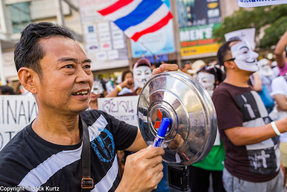 """09 JUNE 2013 - BANGKOK, THAILAND:  A Thai ant-government protester in the White Mask movement pounds on a car hubcap during an anti-government protest at Central World in Bangkok. The White Mask protesters wear the Guy Fawkes mask popularized by the movie """"V for Vendetta"""" and the protest groups Anonymous and Occupy. Several hundred members of the White Mask movement gathered on the plaza in front of Central World, a large shopping complex at the Ratchaprasong Intersection in Bangkok, to protest against the government of Thai Prime Minister Yingluck Shinawatra. They say that her government is corrupt and is a """"puppet"""" of ousted (and exiled) former PM Thaksin Shinawatra. Thaksin is Yingluck's brother. She was elected in 2011 when her brother endorsed her.    PHOTO BY JACK KURTZ"""