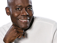 Close-up portrait of an afro American mature man smiling with hand on chin in studio on white isolated background