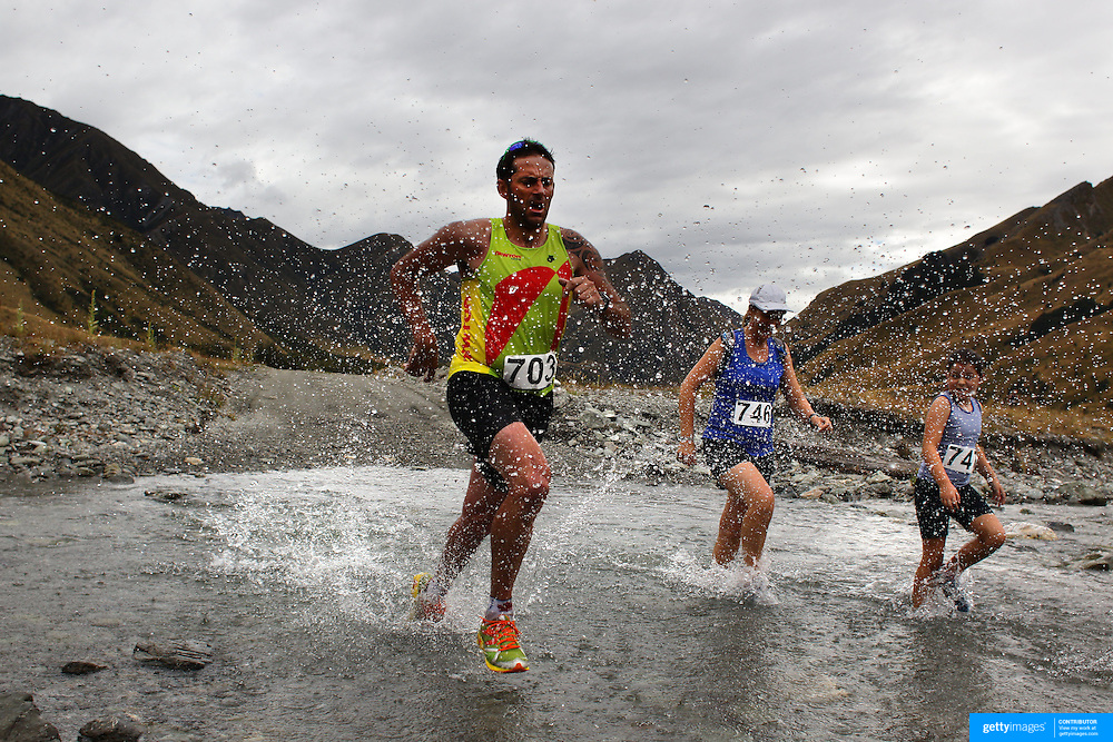 Runner Daniel McDonald crosses  Moke Creek on the Ben Lomond High Country Station during the Pure South Shotover Moonlight Mountain Marathon and trail runs. Moke Lake, Queenstown, New Zealand. 4th February 2012. Photo Tim Clayton