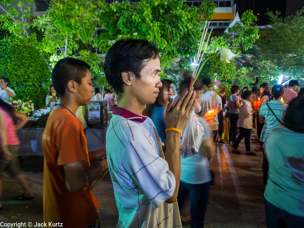 """13 MAY 2013 - BANGKOK, THAILAND:  A man prays during Vesak services at Wat That Thong in Bangkok. Vesak, called Wisakha Bucha in Thailand, is one of the most important Buddhist holy days celebrated in Thailand. Sometimes called """"Buddha's Birthday"""", it actually marks the birth, enlightenment (nirvana), and death (Parinirvana) of Gautama Buddha in the Theravada or southern tradition. It is also celebrated in Cambodia, Laos, Myanmar, Sri Lanka and other countries where Theravada Buddhism is the dominant form of Buddhism.    PHOTO BY JACK KURTZ"""