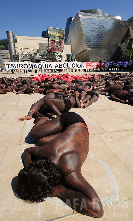 """Pro-animal activists take part in a protest against bullfighting called by Anima Naturalis, Equanimal foundation and CAS-International pro animal groups, in front of the Guggenheim Bilbao museum, in the Northern Spanish Basque city of Bilbao, on August 21, 2010, ahead of the Aste Nagusia festivities. Banner reads """"Bullfighting Abolition"""". PHOTO / Rafa Rivas"""