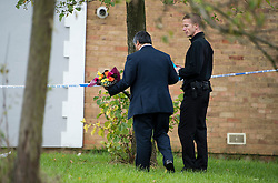 ©  London News Pictures. 15/10/2012. Harlow, UK. A man laying flowers at the scene on Barn Mead, Harlow, Essex where three children and a woman have died and three others are in hospital following a house fire. Two boys aged 13 and six, a girl aged 11 and the woman were declared dead at the scene. A nine-year-old boy and a three-year-old girl have serious burns and a man has minor burns. Photo credit : Ben Cawthra/LNP