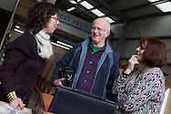 England, Emsworth, The Boat Project. 25  February  2011. Gwen Van Spijk takes details from a couple who have made a donation to The Boat Project.