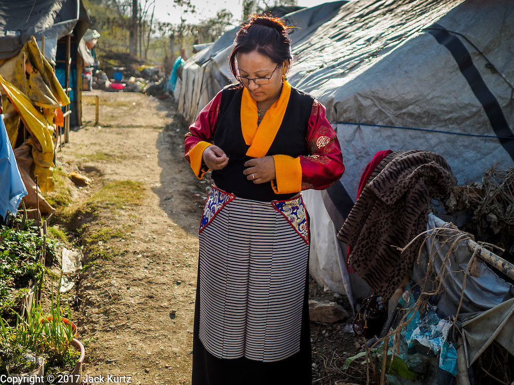 04 MARCH 2017 - KATHMANDU, NEPAL: A Nepali Sherpa woman in an IDP camp in the center of Kathmandu puts on her fancy clothes before going to a Tibetan New Years ceremony at a Buddhist temple about 10 miles from the camp. The camp opened days after the April 2015 earthquake devastated Nepal, killing almost 9,000 people. At its peak, about 1,800 families lived in the camp. The camp is still open nearly two years after the earthquake, about 400 families currently live in the camp. Camp residents say the Kathmandu municipal government is trying to close the camp and is encouraging residents to find new housing. They said the government is cutting off services to the camp and last week stopped the free distribution of water, although water can be purchased for delivery. Most of the people in the camp came to Kathmandu from rural villages in the mountains in the weeks after the earthquake. Many of the residents of the camp, technically homeless, have found work in Kathmandu's bustling construction industry, rebuilding homes destroyed in the earthquake.       PHOTO BY JACK KURTZ