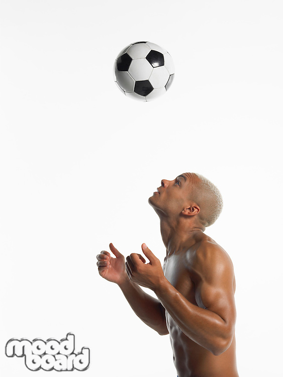 Football player looking up at ball in mid-air side view