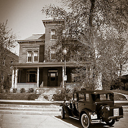"""Crown Point Jail Lake County Indiana with a Ford Model A antique car parked in front. Photo is high resolution black and white and has been processed in old vintage style. In 1934 John Dillinger escaped from the Lake County jail in this building. In 2008 Universal Studios filmed parts of the movie Public Enemies with Johnny Depp. The jail is open to the public for tours and goes past Dillinger's cell and also where filming was done. Crown Point is located in Northwest Indiana with a population of over 37,000. Crown Point and Lake County are about 50 miles from Chicago and are considered part of the """"Chicagoland"""" area. Crown Point has a traditional small town America feel with a main street consisting of the old Lake County Courthouse surrounded by numerous small businesses, known as """"the square"""", including a theater, ice cream shop, antique stores, and restaurants."""