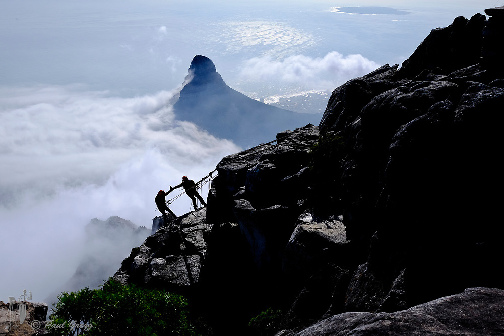 Table Mountain,Cape Town, South Africa. Climbers prepare to abseil down the rock face on table mountain. Lion's Head emerges through the clouds in the background.