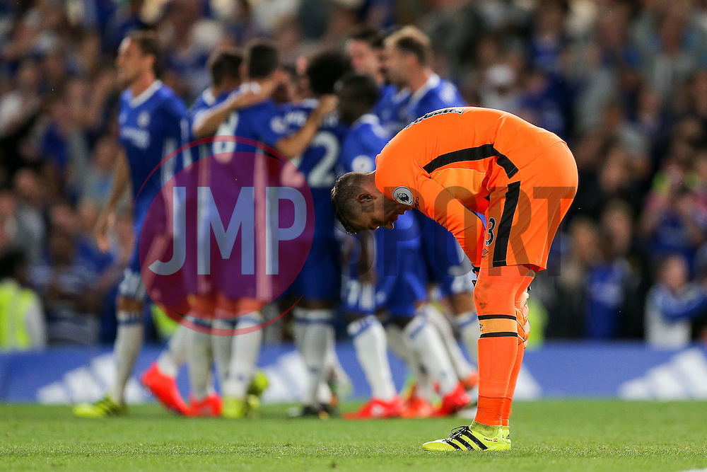 Adrian of West Ham United looks dejected as Eden Hazard of Chelsea celebrates scoring a goal from the penalty spot to make it 1-0 - Rogan Thomson/JMP - 15/08/2016 - FOOTBALL - Stamford Bridge Stadium - London, England - Chelsea v West Ham United - Premier League Opening Weekend.