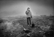 Worker burning trash in a hazy at dusk along a levee at the edge of Wuhai, Inner Mongolia, China.