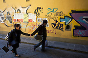 An Italian couple walk along a side street near Florence's Piazza Santa Croce. Graffiti lines the far wall and the man partner looks at the writing and scrawls sprayed by markers and aerosol as he seemingly pulls his lady friend or wife along the road.