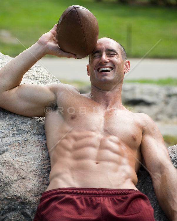 Guy leaning on a rock holding a football laughing with his eyes closed