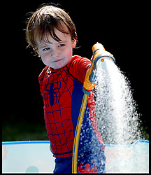 Image ©Licensed to i-Images Picture Agency. 05/07/2014. London, United Kingdom. Isaac Attwood 2, cools down in the paddling pool in the hot weather. Picture by Andrew Parsons / i-Images
