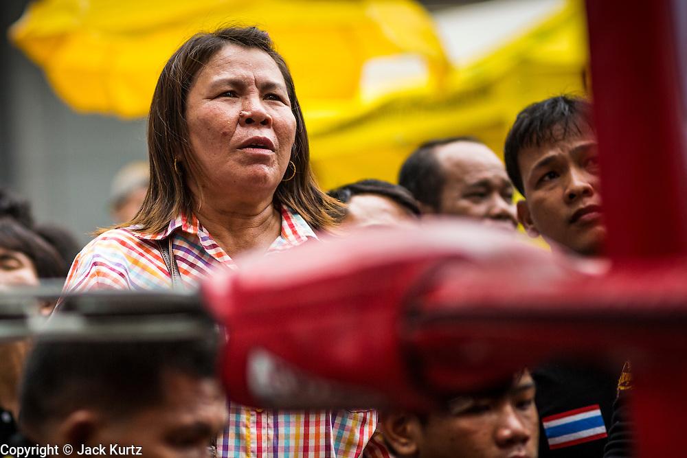 28 JULY 2013 - BANGKOK, THAILAND:  A Thai woman watches the action through the ropes at the ASEAN Muay Thai Championship at MBK shopping center in Bangkok.      PHOTO BY JACK KURTZ