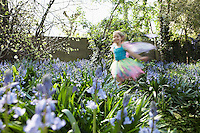 Young girl (5-6) running in flower garden wearing fairy costume motion blur