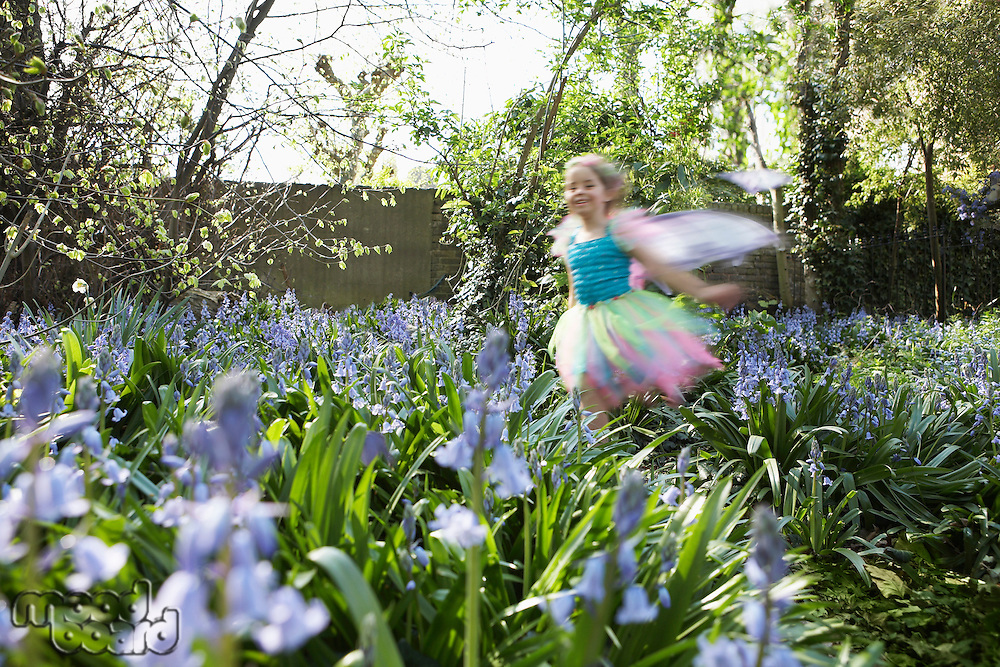 Young girl (5-6) running in flower garden wearing fairy costume motion blur