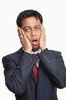 Portrait of shocked young businessman against white background