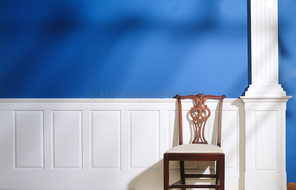 Chippendale chair against white wood paneled chair rail with blue wall