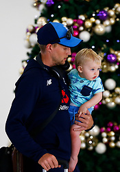 England's Joe Root with his son Alfred as the team arrive at Adelaide Airport.