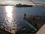 A container ship headed outbound toward the ocean with a light load crosses the bow of a Washington State Ferry in Puget Sound with a few tourists watching at the rail.