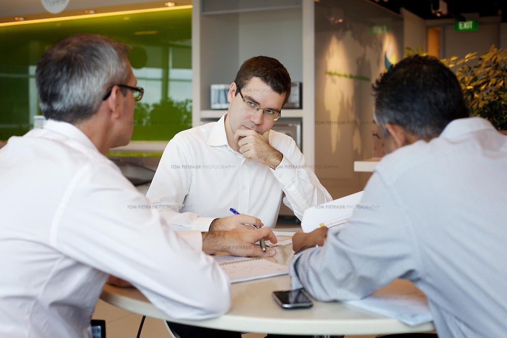 Staff meet in a Singapore office. <br /> Photo: Tom Pietrasik.Singapore. 2011