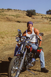 man sitting on a motorcycle on a dirt road