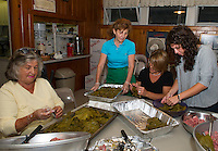 "Angie Argiropolis, Bessie Kafanelis and Christine and Samantha Kemos prepare ""Dolmathes"" (stuffed grape leaves) in preparation of the 26th annual Greek Summer Festival at Taxiarchai Greek Orthodox Church in Laconia on Saturday starting at 10am.  (Karen Bobotas/for the Laconia Daily Sun)"