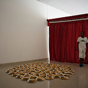 "A volunteer at a community centre in Bujumbura, displays meals for students from Bujumbura University on the run from the National Police after having their improvised camp outside the American embassy dismantled. The students had moved to the area in early May because, they claim, the US authorities ensure their security, after their university was closed amid anti-government protests. The government closed the university at the end of April, citing ""insecurity""."