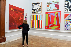 """© Licensed to London News Pictures. 08/06/2017. London, UK. A visitor views (L) """"Red Sea"""" by Barbara Rae RA, (C) """"You Can't Fire A Cannon From A Rowing Boat"""" by Christine Stark and (R) """"Hold Fast"""" by Vanessa Jackson RA. Preview of the Summer Exhibition 2017 at the Royal Academy of Arts in Piccadilly.  Co-ordinated by Royal Academician Eileen Cooper, the 249th Summer Exhibition is the world's largest open submission exhibition with around 1,100 works on display by high profile and up and coming artists.<br />  Photo credit : Stephen Chung/LNP"""
