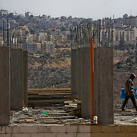 Palestinian workers work at the Al Reehan neighborhood new neighborhood as is seen in the back the city of Ramallah...Photo by Olivier Fitoussi.