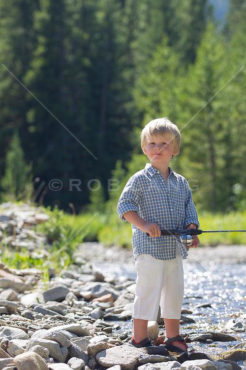 blond little boy by a stream in Montana