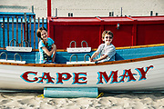 Kids pose in a lifeguard rescue boat on the beach in Cape May, New Jersey, USA