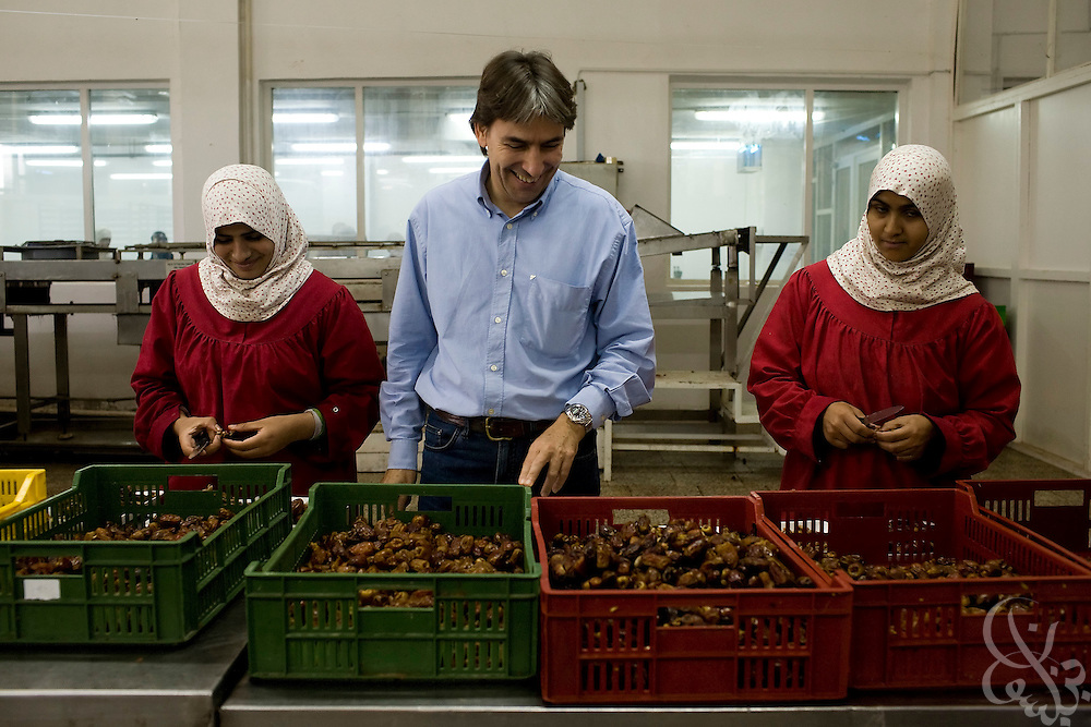 Helmy Abouleish, (c) Managing Director of the leading Egyptian Organic foods and products producer, Sekem Group, watches as Egyptian women prepare fresh dates for market at the Sekem farm Nov 4, 2008 in Belbeis, Egypt. Helmy's father, Dr. Ibrahim Abouleish founded the project in 1977 on what was then barren desert, and since has grown it into a lush oasis ecompassing several farms, production plants, schools and even a local medical facility.