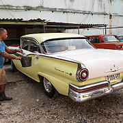 Taking care of a 1957 Ford Fairlane, one of many classic, colorful cars offer their taxi services to tourists.  <br /> Photography by Jose More