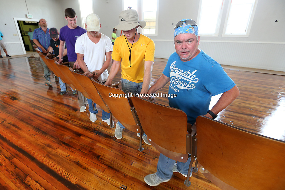 David Warren, a worker with Sullivan Enterprises out of Magee Mississippi, walks on the original floor that was discovered during the renovation and refinished, as he and his fellow workers bring in the first row of seating into the auditorium of Lawhow Elementary School.