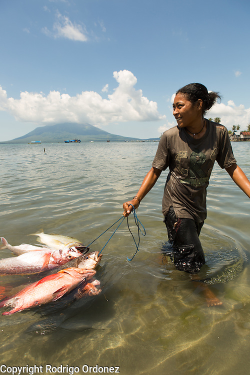 Siti Rofi'ah's step daughter, Nur San, 22, brings fish ashore from the boat of Jainudin One, who just returned home after fishing overnight. They live in Lewoleba, Nubatukan subdistrict, Lembata district, East Nusa Tenggara province, Indonesia.