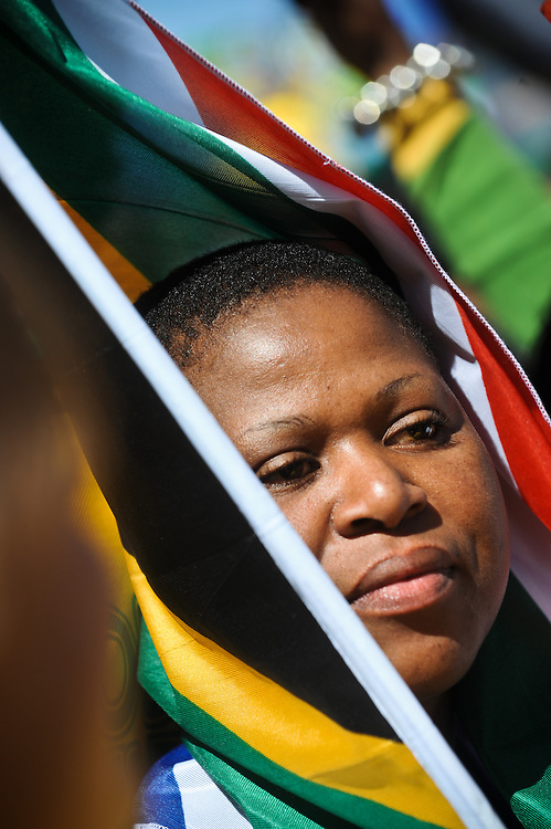 "A woman wraps the South African flag around her head at the ""United We Shall Stand"" rally for the South African national soccer team, Bafana Bafana, Tuesday, June 9, 2010 in Johannesburg, South Africa. South Africa is hosting the FIFA World Cup, which begins June 11. Photo by Bahram Mark Sobhani"