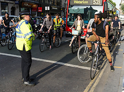 © Licensed to London News Pictures. 21/08/2013. London, UK. A community support officer conducts safety checks on road users at Holborn traffic lights yards from the spot where cyclist Alan Neve was killed by a tipper truck on the 15th July. The checks are to highlight the need to leave room for cyclists at traffic lights - the cyclist in this picture (right) has has overshot the area reserved for cyclists.  Photo credit : Richard Isaac/LNP