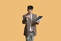 Portrait of a young businessman pointing while holding clipboard over colored background