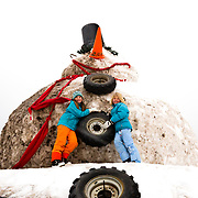 Clara McGee and Jade Goodrich pose for a portrait on a giant snowman near Teton Village, Wyoming.