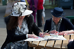 LIVERPOOL, ENGLAND - Friday, April 9, 2010: A female race-goers pick their horses on Ladies' Day during the second day of the Grand National Festival at Aintree Racecourse. (Pic by David Rawcliffe/Propaganda)